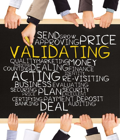 validating: Photo of business hands holding blackboard and writing VALIDATION word cloud Stock Photo