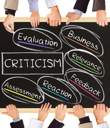 criticism: Photo of business hands holding blackboad and writing CRITICISM concept
