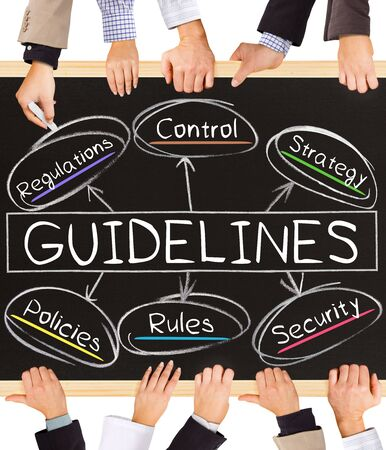 guidelines: Photo of business hands holding blackboard and writing GUIDELINES concept Stock Photo