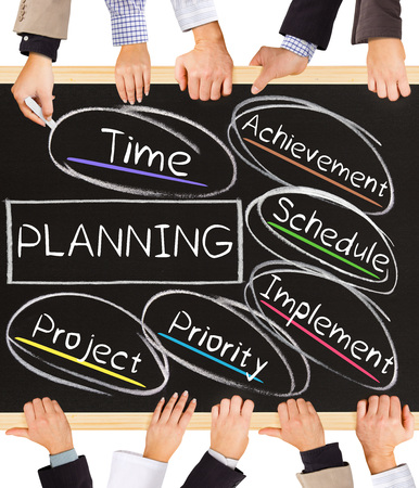 planning diagram: Photo of business hands holding blackboard and writing PLANNING diagram