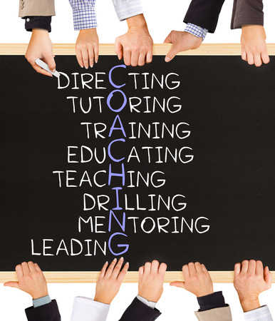 Photo of business hands holding blackboard and writing COACHING concept