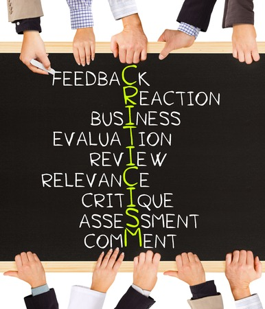 criticism: Photo of business hands holding blackboard and writing CRITICISM concept