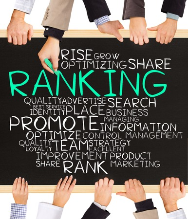 Photo of business hands holding blackboard and writing RANKING word cloud