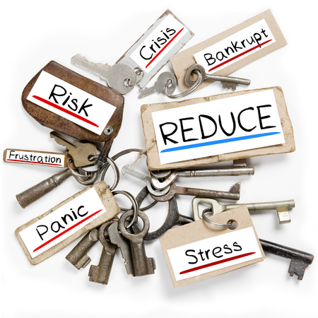 Photo of key bunch and paper tags with REDUCE conceptual words Stock Photo