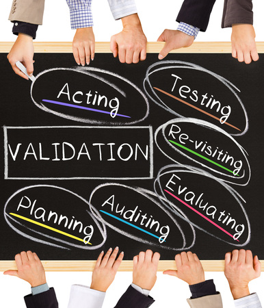 validation: Photo of business hands holding blackboard and writing VALIDATION diagram Stock Photo