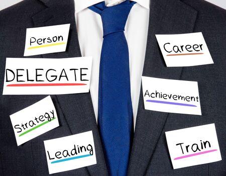 delegar: Foto de traje y corbata con concepto DELEGADO tarjetas de papel