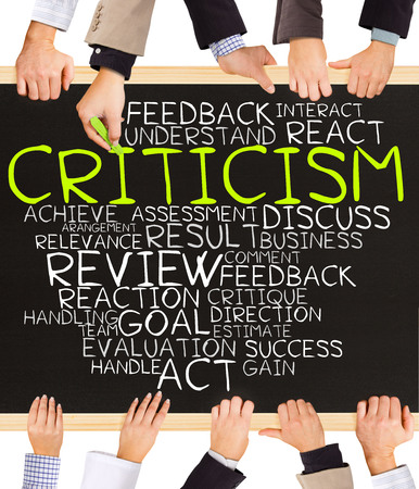 Photo of business hands holding blackboard and writing CRITICISM concept