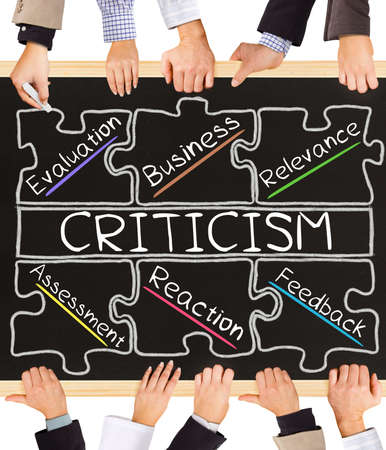 criticize: Photo of business hands holding blackboard and writing CRITICISM concept