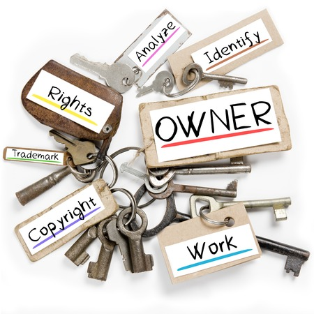 ownership and control: Photo of key bunch and paper tags with OWNER conceptual words Stock Photo