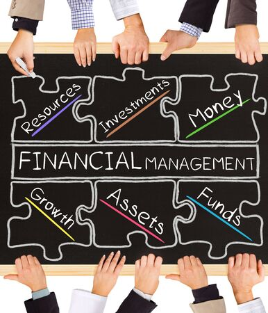 basic scheme: Photo of business hands holding blackboard and writing FINANCIAL MANAGEMENT concept Stock Photo
