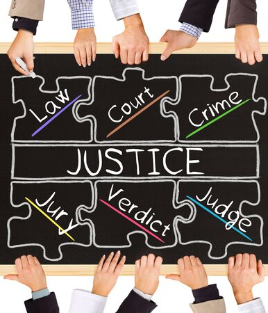 schema: Photo of business hands holding blackboard and writing JUSTICE concept Stock Photo