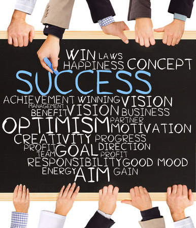 schema: Photo of business hands holding blackboard and writing SUCCESS concept Stock Photo