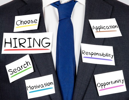 new recruit: Photo of business suit and tie with HIRING conceptual words written on paper cards
