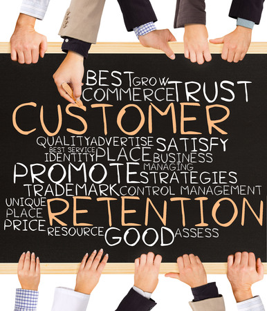 retention: Photo of business hands holding blackboard and writing CUSTOMER RETENTION concept