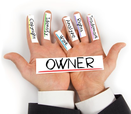 authorship: Photo of hands holding paper cards with OWNER concept words