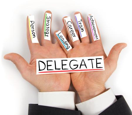delegar: Foto de las manos que sostienen las tarjetas de papel con palabras de concepto DELEGADO Foto de archivo