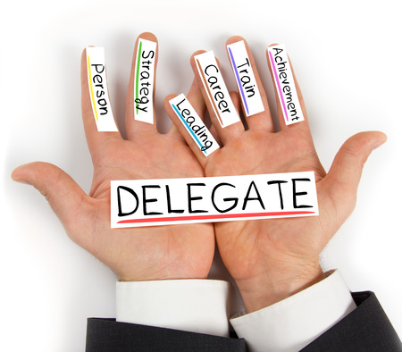 delegate: Photo of hands holding paper cards with DELEGATE concept words Stock Photo