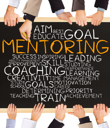 mentoring: Photo of business hands holding blackboard and writing MENTORING concept