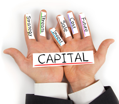 cashflow: Photo of hands holding paper cards with CAPITAL concept words