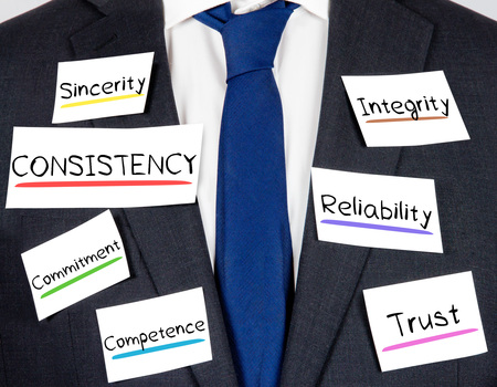 consistency: Photo of business suit and tie with CONSISTENCY conceptual words written on paper cards