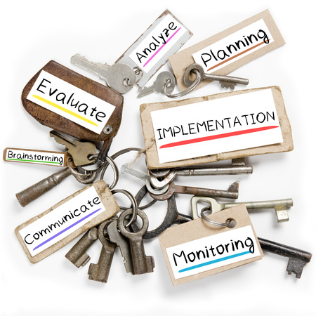 Photo of key bunch and paper tags with IMPLEMENTATION conceptual words