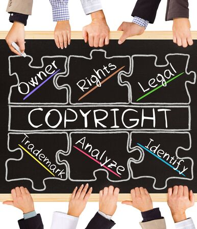 authorship: Photo of business hands holding blackboard and writing COPYRIGHT concept Stock Photo