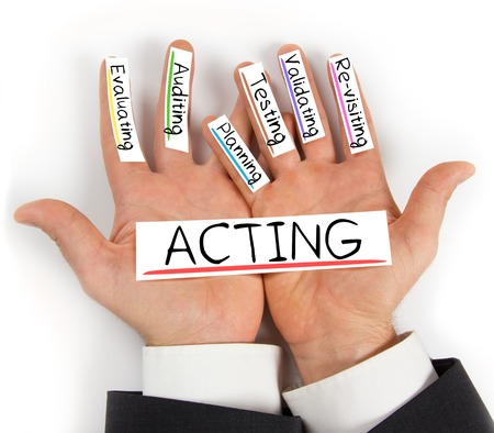 validating: Photo of hands holding paper cards with ACTING concept words