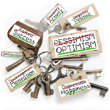 pessimism: Photo of key bunch and paper tags with PESSIMISM OPTIMISM conceptual words
