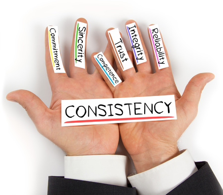 consistency: Photo of hands holding paper cards with CONSISTENCY concept words Stock Photo