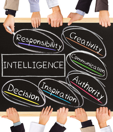 relation: Photo of business hands holding blackboard and writing INTELLIGENCE concept Stock Photo