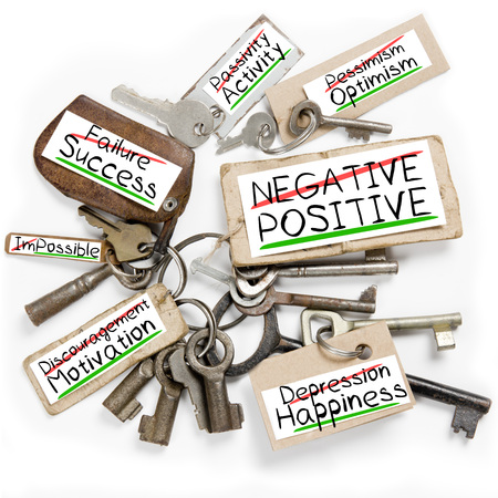 negative: Photo of key bunch and paper tags with NEGATIVE POSITIVE conceptual words