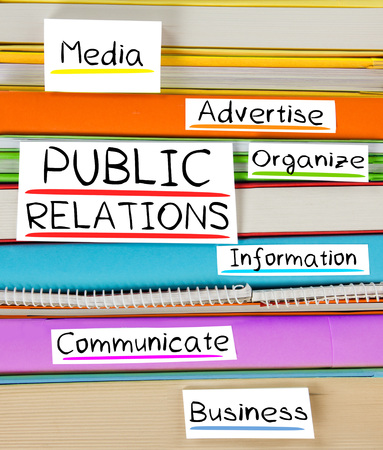 news values: Photo of colorful book stack with bookmarks and labels with PUBLIC RELATIONS conceptual words