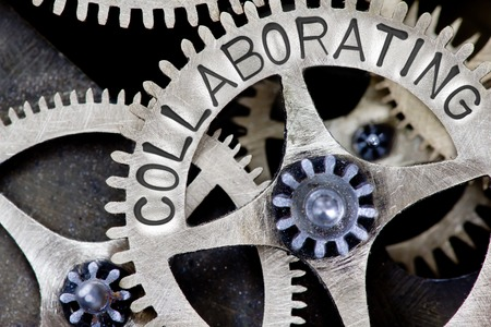 collaborating: Macro photo of tooth wheel mechanism with COLLABORATING concept words Stock Photo
