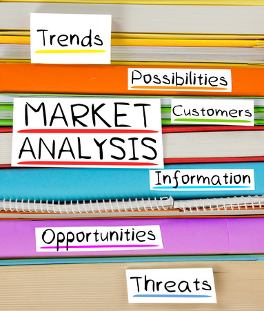 Photo of colorful book stack with bookmarks and labels with MARKET ANALYSIS conceptual words