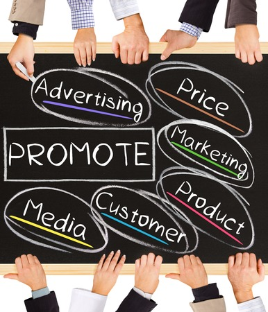 promote: Photo of business hands holding blackboard and writing PROMOTE concept Stock Photo