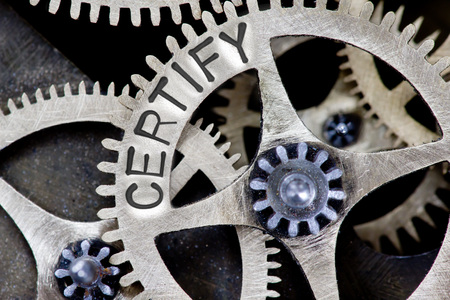 certify: Macro photo of tooth wheel mechanism with CERTIFY concept letters Stock Photo
