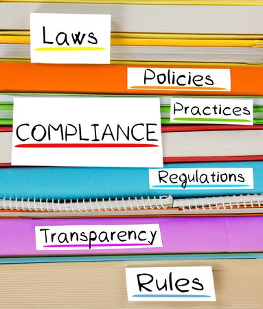 governance: Photo of colorful book stack with bookmarks and labels with COMPLIANCE conceptual words