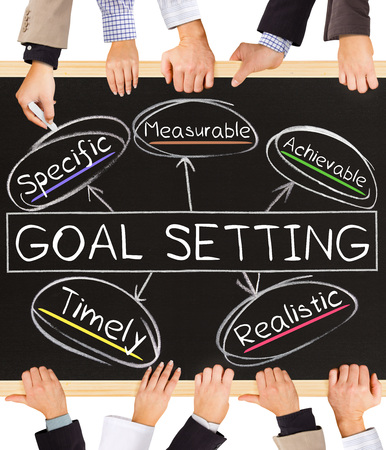 achievable: Photo of business hands holding blackboard and writing GOAL SETTING concept
