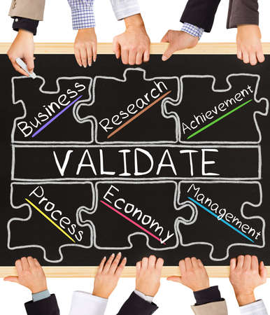 validating: Photo of business hands holding blackboard and writing VALIDATE concept