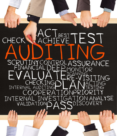 auditing: Photo of business hands holding blackboard and writing AUDITING concept