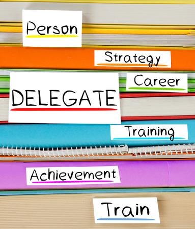 delegar: Foto de libro colorida de la pila con marcadores y etiquetas con el delegado palabras conceptuales
