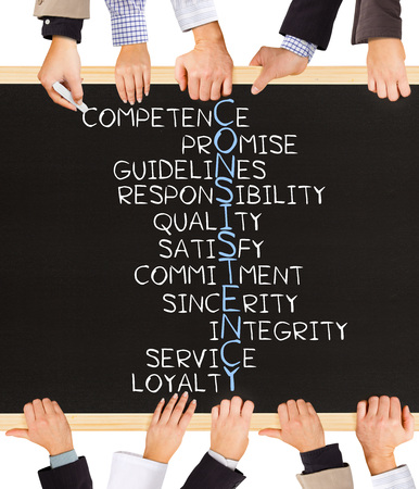consistency: Photo of business hands holding blackboard and writing CONSISTENCY concept