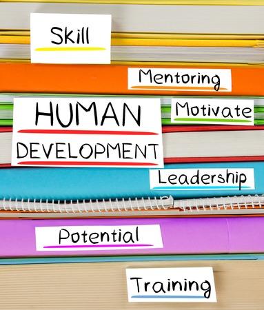relaciones laborales: Foto de libro colorida de la pila con marcadores y etiquetas con el desarrollo humano palabras conceptuales Foto de archivo
