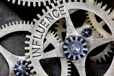 influence: Macro photo of tooth wheel mechanism with INFLUENCE concept letters Stock Photo