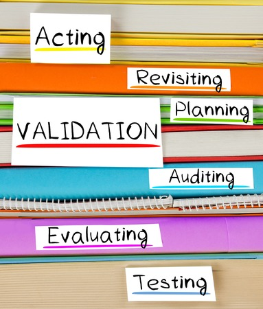 validating: Photo of colorful book stack with bookmarks and labels with VALIDATION conceptual words Stock Photo