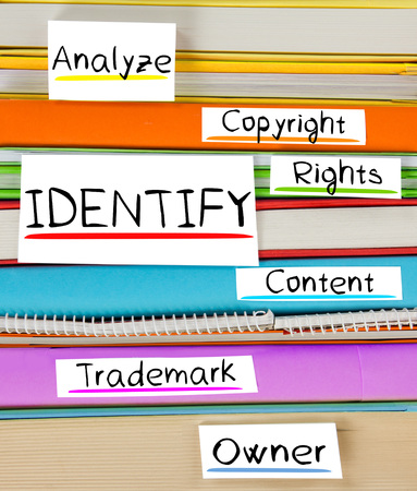 authorship: Photo of colorful book stack with bookmarks and labels with IDENTIFY conceptual words