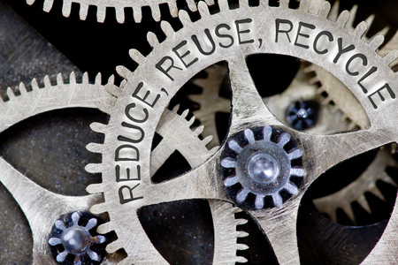 reduce: Macro photo of tooth wheel mechanism with REUSE, REDUCE, RECYCLE concept letters