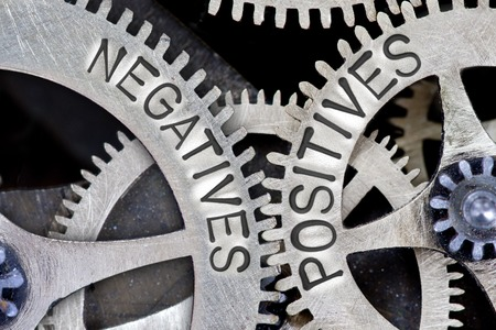 positives: Macro photo of tooth wheel mechanism with NEGATIVES, POSITIVES letters Stock Photo