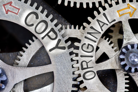 Macro foto van tandwiel mechanisme met pijlen en COPY, ORIGINELE concept woorden