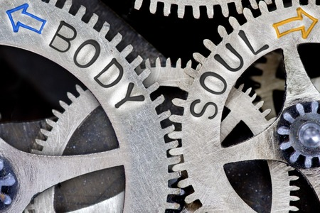 body and soul: Macro photo of tooth wheel mechanism with arrows and BODY, SOUL concept words Stock Photo